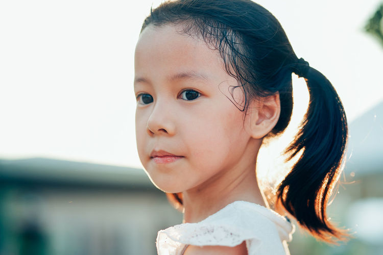 Close-up portrait of cute girl looking away