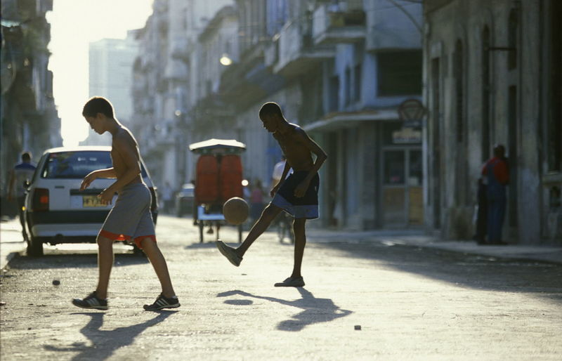 Shirtless Boys Playing Soccer On Street In City