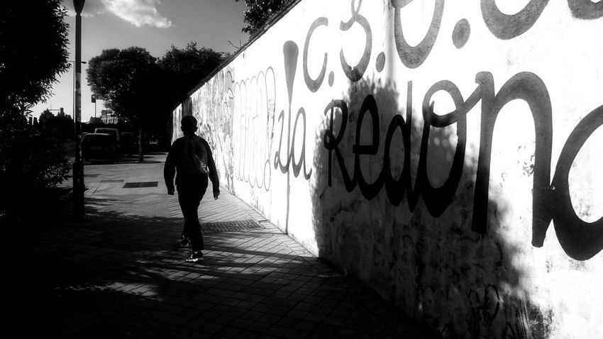 City Life Cityscape Architecture Black And White Blackandwhite Building Exterior Built Structure City Day Footpath Full Length Lifestyles Light And Shadow Men Monochrome One Person Outdoors Real People Rear View Shadow Sunlight Text Walking Wall - Building Feature