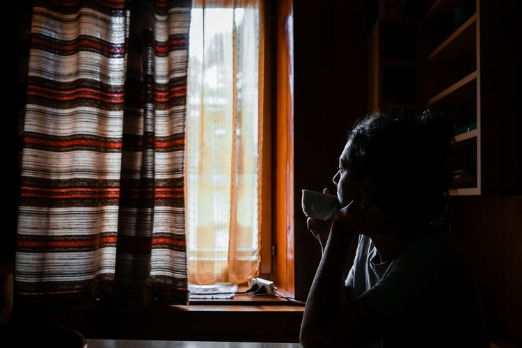 Side view of woman drinking tea while sitting at home