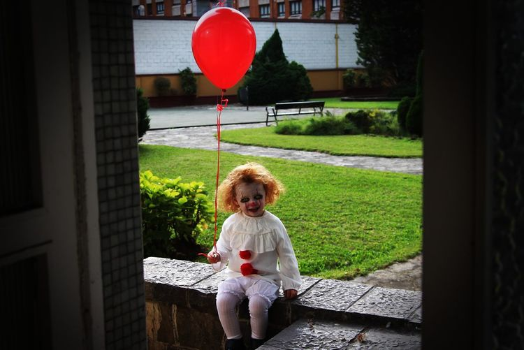 One Person Full Length People Childhood Children Only Curly Hair Grass Day Child Sitting Outdoors Sky Halloween Clown IT Pennywise Horror Costume