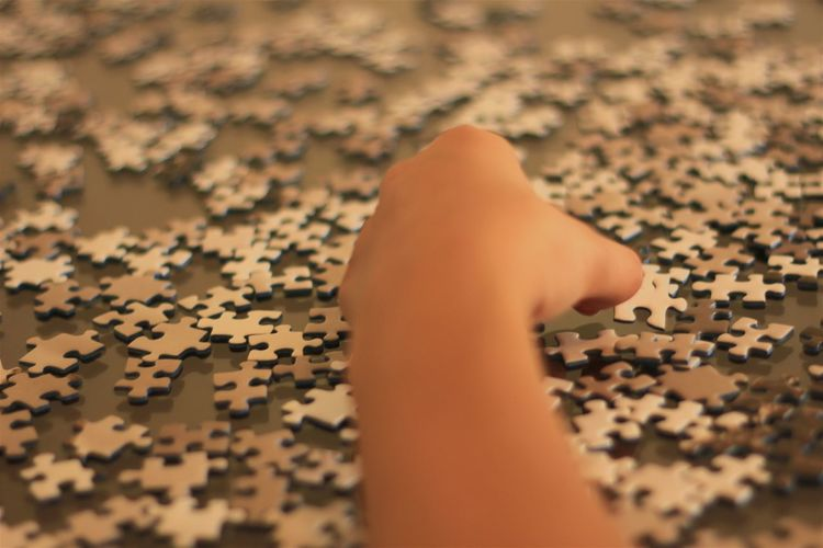 Cropped Image Of Hand Against Jigsaw Puzzle