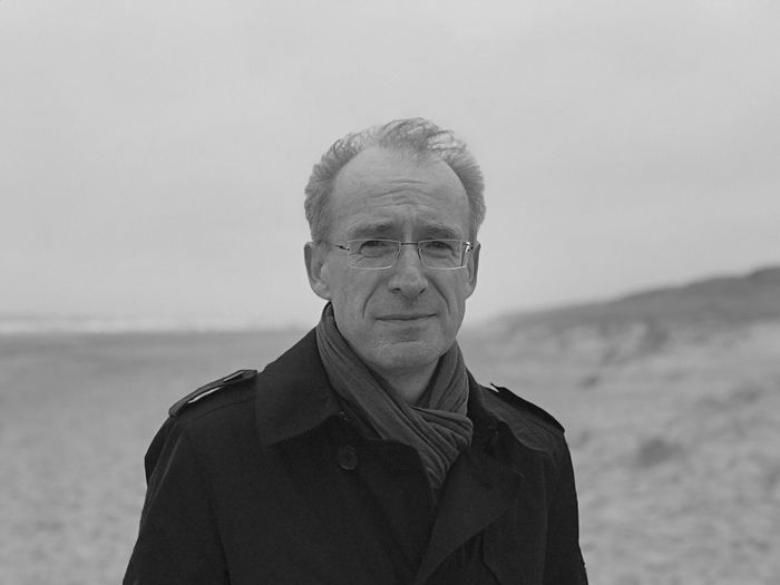 Portrait of man standing at beach against sky