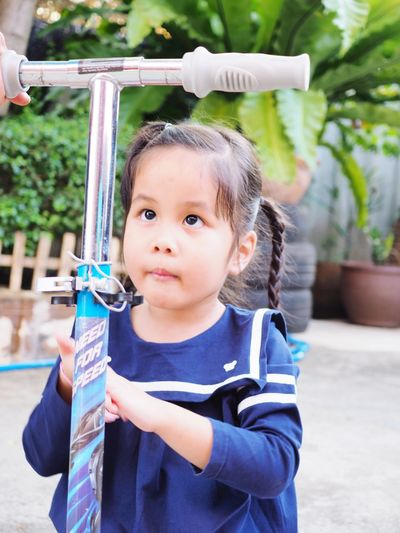 Side view of girl looking away while standing by push scooter