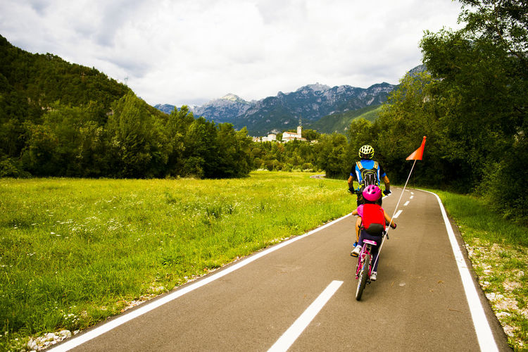 Rear view of girl with father riding bicycle on road