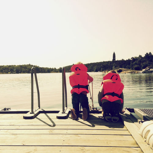 Two children with life vests looking into the water on the pier. Pier Childhood Day Lake Leisure Activity Lifevest Nature Outdoors Sky Sunlight Two People Water