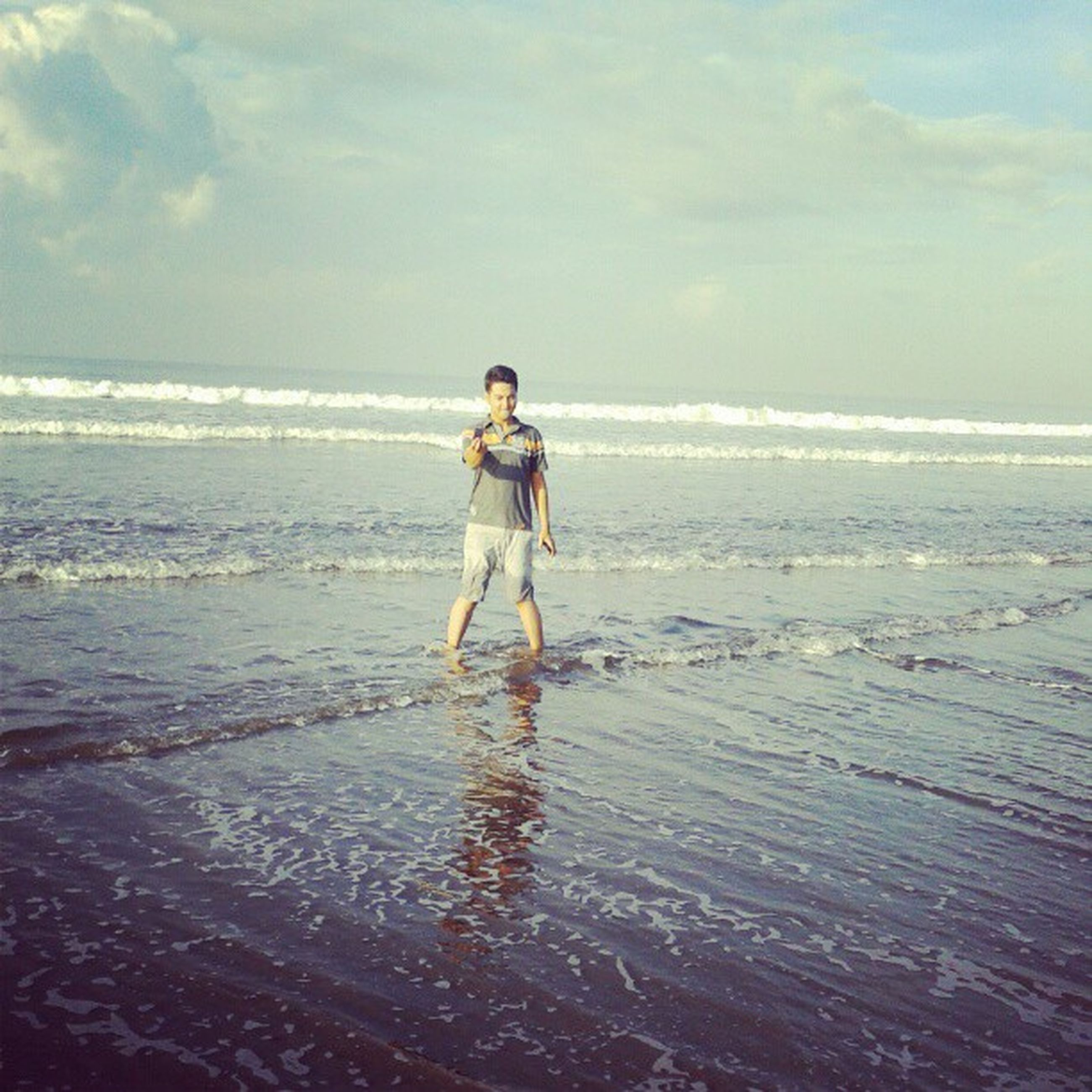 beach, sea, horizon over water, water, full length, shore, sky, lifestyles, leisure activity, sand, casual clothing, childhood, vacations, standing, tranquility, rear view, tranquil scene, scenics