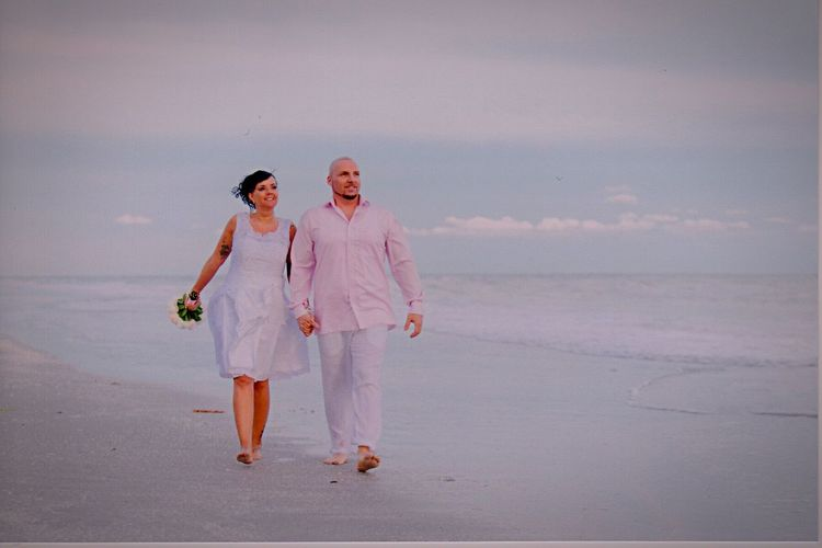 Full length couple walking at beach against sky during sunset