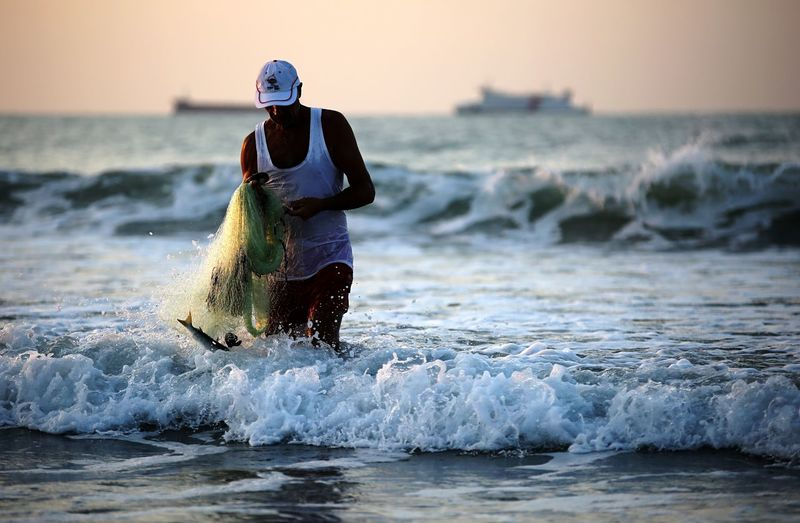 Man holding fishing net while walking in sea against sky during sunset