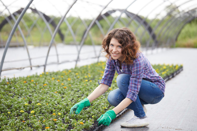Portrait of smiling young woman working in greenhouse