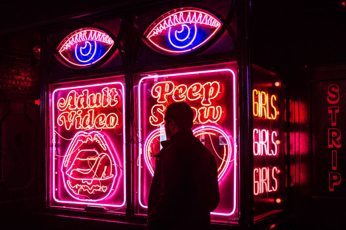 REAR VIEW OF WOMAN STANDING AGAINST ILLUMINATED SIGN