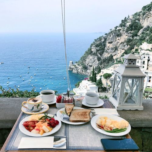 Breakfast served on table at restaurant with sea in background