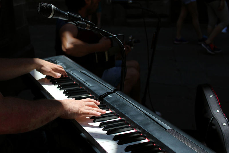 Cropped hand of man playing piano by microphone