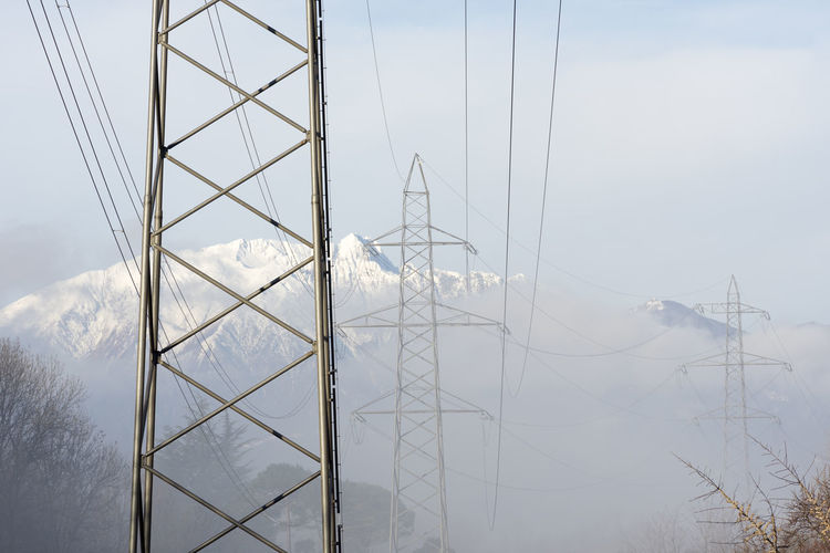 Electricity Pylon Against Snowcapped Mountain And Sky