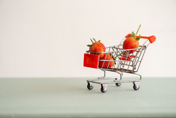 Closeup strawberries in the shopping trolley. Cart carrying the strawberry with the isolated background Shopping Cart Healthy Eating Fruit Studio Shot Wellbeing Strawberry Close-up White Background