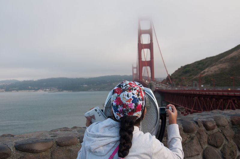 Rear view of girl looking through coin-operated binoculars against golden gate bridge