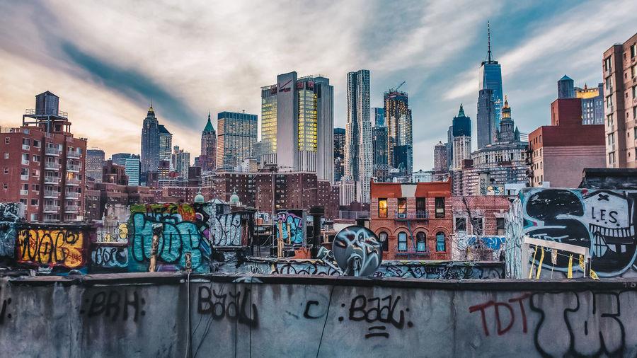 Graffiti on modern buildings in city against sky