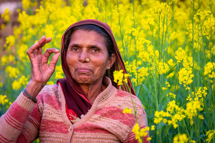 Portrait of woman standing on yellow flowering plants