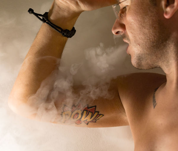 Close-up of shirtless man exhaling smoke against wall