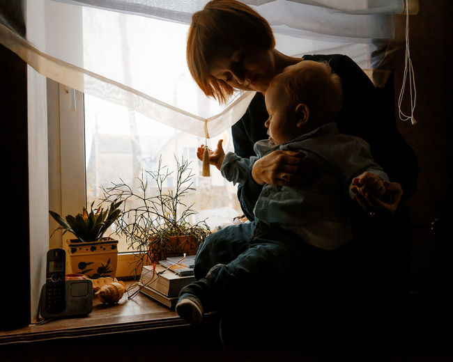 Mother and baby sitting on the window Baby Bonding Casual Clothing Childhood Day Family With One Child Home Interior Indoors  Leisure Activity Lifestyles Real People Togetherness Young Adult Young Women The Portraitist - 2017 EyeEm Awards