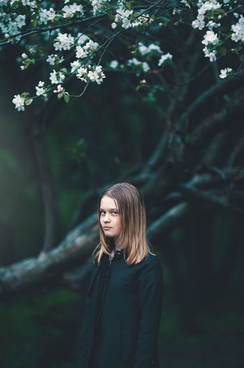 Portrait of girl standing at forest