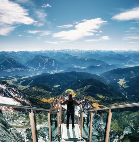 Young man with backpack stands on observation deck of skywalk rope bridge Dachstein Mountains and enjoys the landscape in Austria Alpine Austria Dachstein Alps Backpacker Beauty In Nature Cloud - Sky Hiking Landscape Leisure Activity Lifestyles Men Mountain Mountain Range Nature One Person Outdoors Railing Real People Scenics Sky Tranquil Scene Go Higher