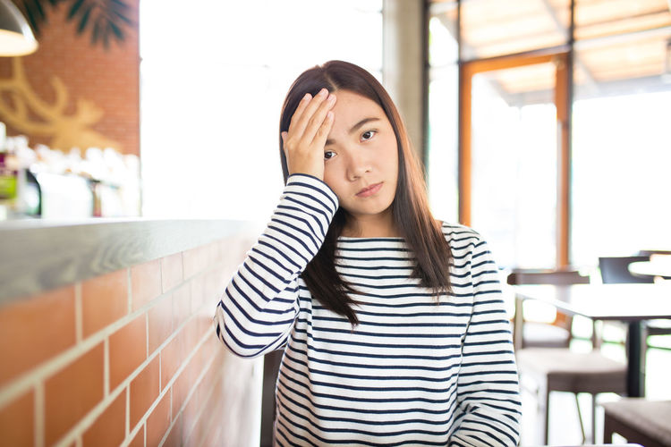 Portrait of young woman suffering from headache while sitting in restaurant