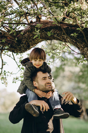 Father and son on plant against trees