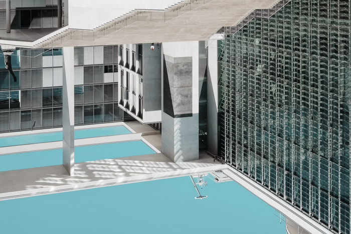 HIGH ANGLE VIEW OF SWIMMING POOL BY BUILDINGS