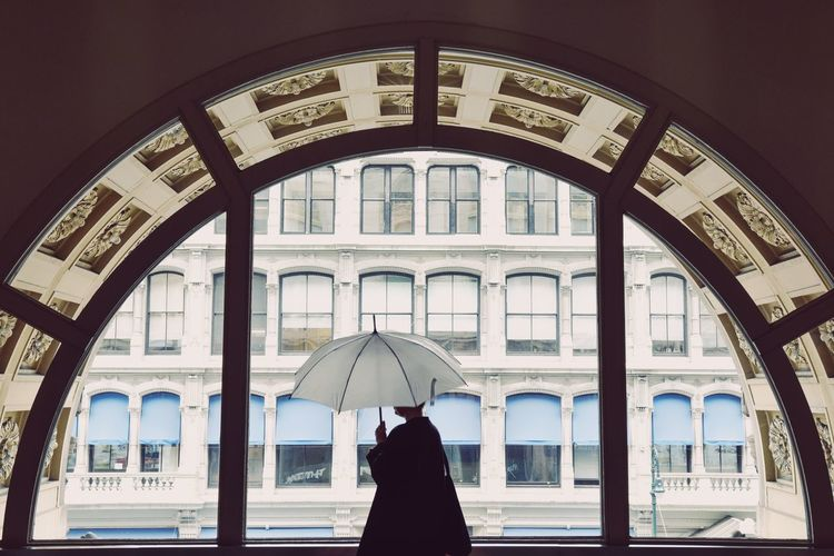 Woman holding umbrella while walking against arch