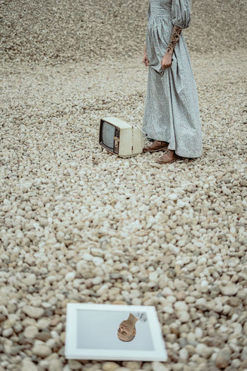 Low section of woman standing with television set and mirror on field