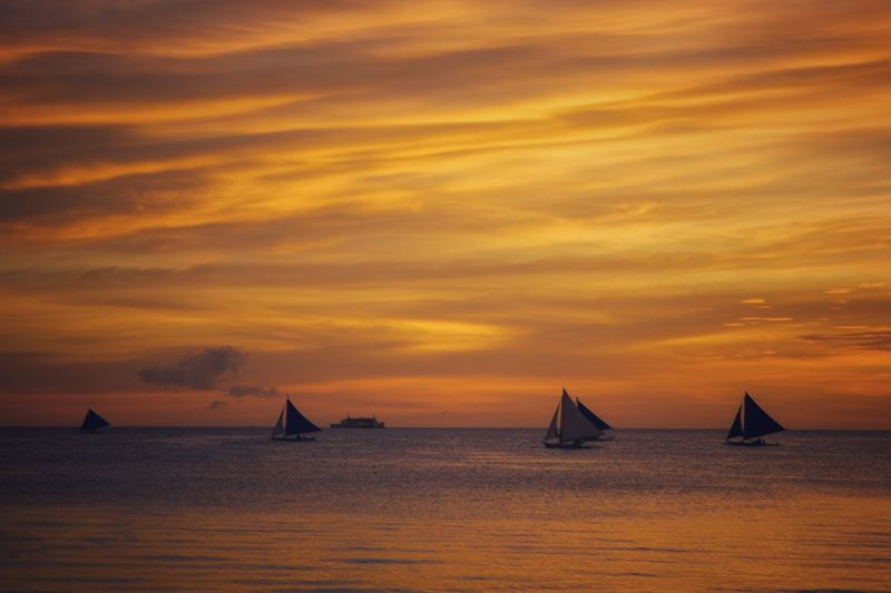 Sailboats sailing on sea against orange sky