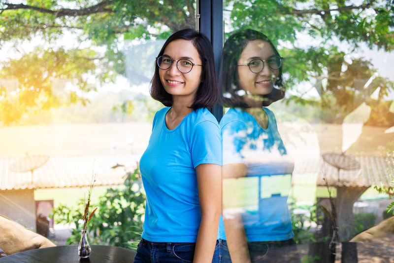 Portrait of smiling woman reflecting on window