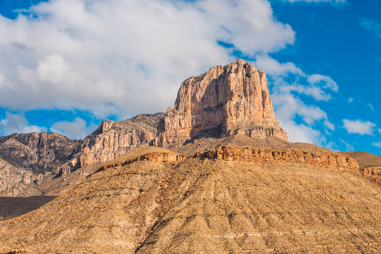 Rock formations on mountain against cloudy sky