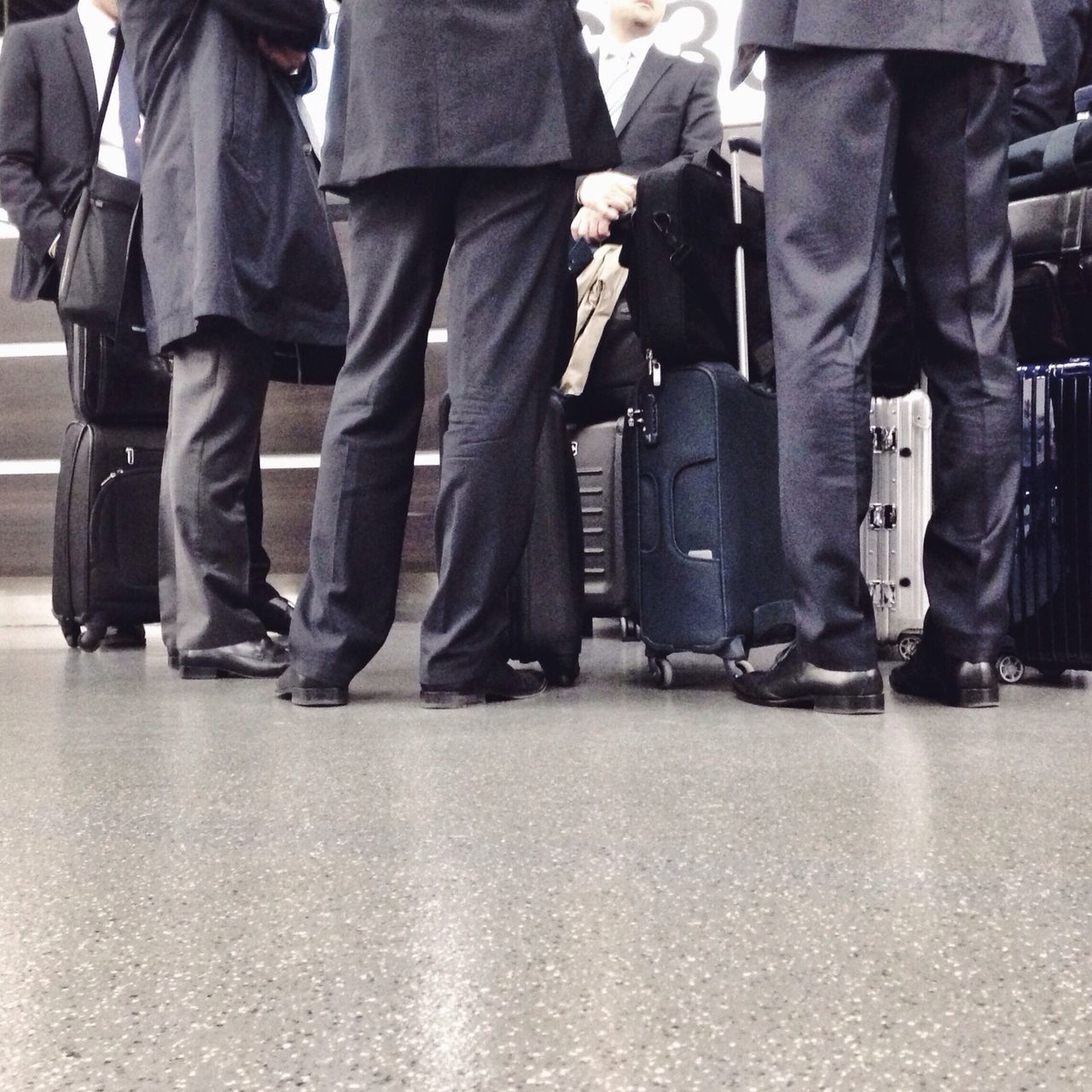 Low section of businessmen waiting at airport