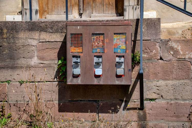 Close-up of old telephone booth against wall