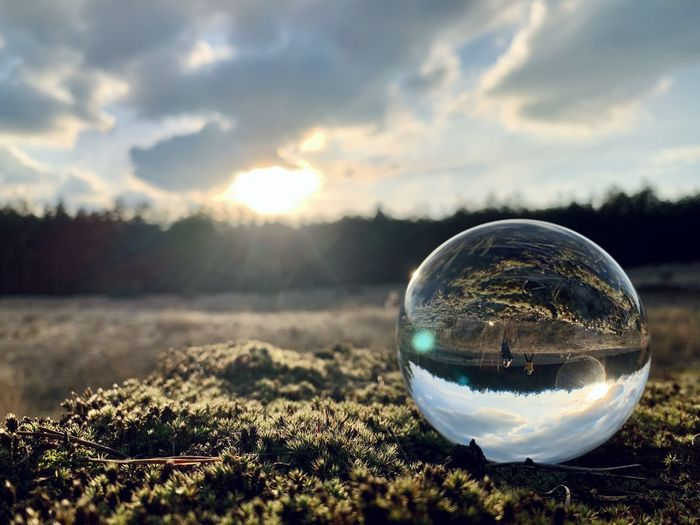 Reflection of crystal ball on glass against sky during sunset