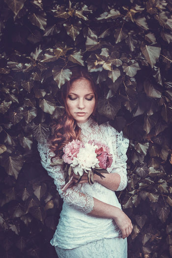 Beautiful bride standing amidst plants