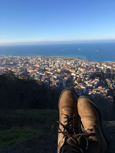 Shoes against cityscape in sunny day