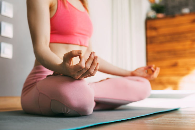 A young woman sits in the lotus position and meditates at home or in a yoga class and meditates.