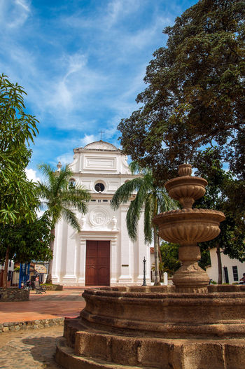 A white church in Santa Fe de Antioquia, Colombia Antioquia Architecture Attraction Building Catholic Catholicism Christian Christianity Church Colombia Colonial Cultural Culture Day Heritage Historic Historical History Landmark Old Outdoors Religion Santa Fe Town Tree