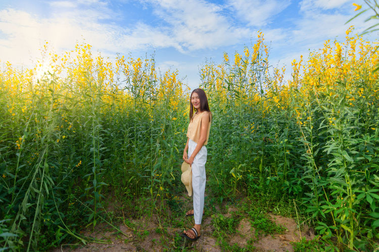 Portrait of young woman standing against flowering plants