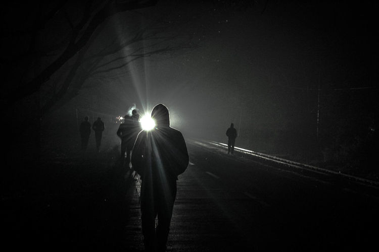 Silhouette people walking on road at night