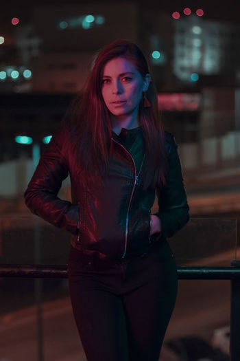 Beautiful young woman standing in city at night
