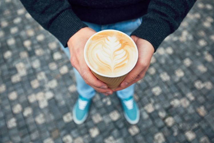 Low section of woman holding coffee in cup