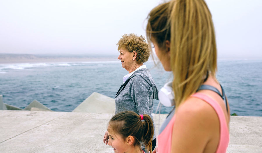 Girl with mother and grandmother walking on pier