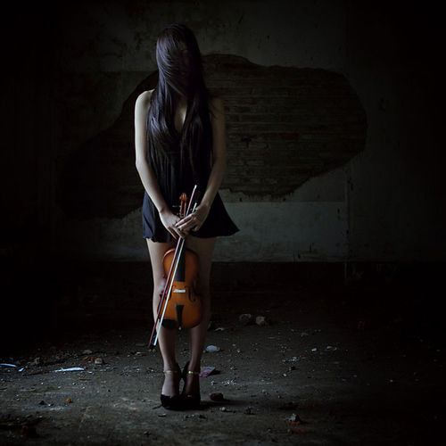 Woman Holding Violin On Street At Night