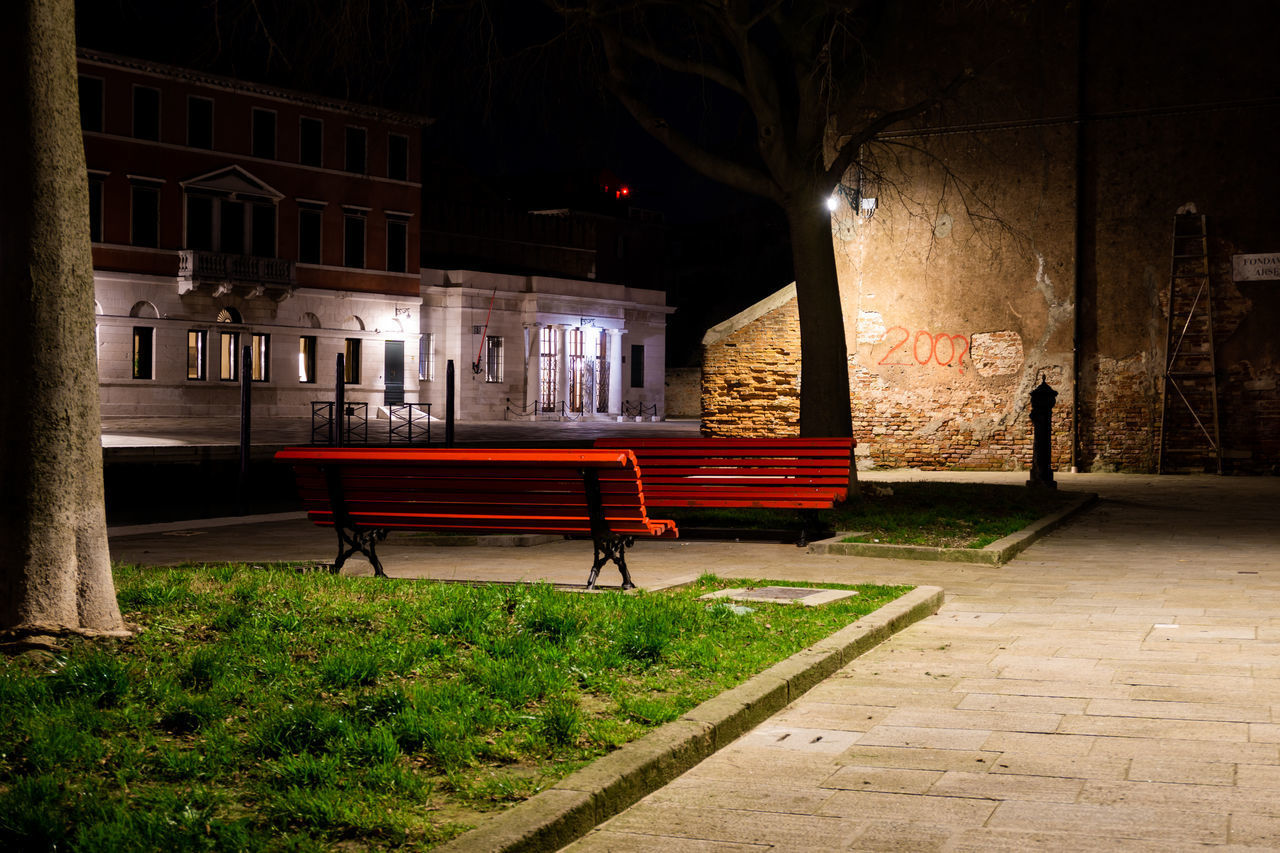 EMPTY BENCH BY ILLUMINATED STREET LIGHT IN CITY