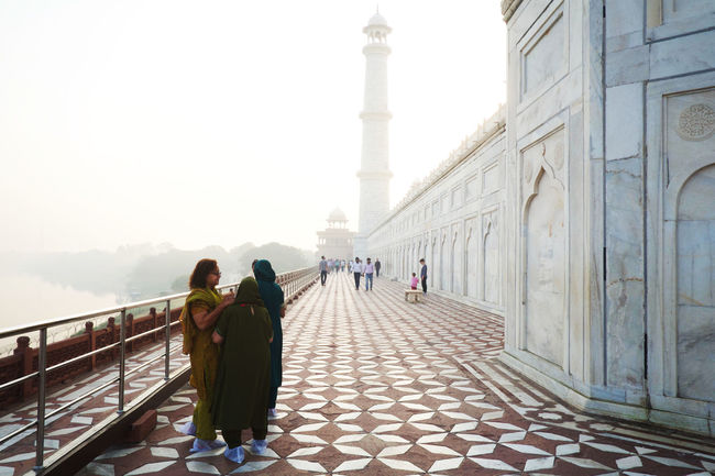 local women exploring the Taj Mahal Architecture Built Structure Real People Group Of People Women Adult Travel Destinations Travel Tourism People Rear View Sky Day Minaret Family Women Talking Walking Taj Mahal Morning Light Morning Mist Mist Agra View Path Moghul Architecture