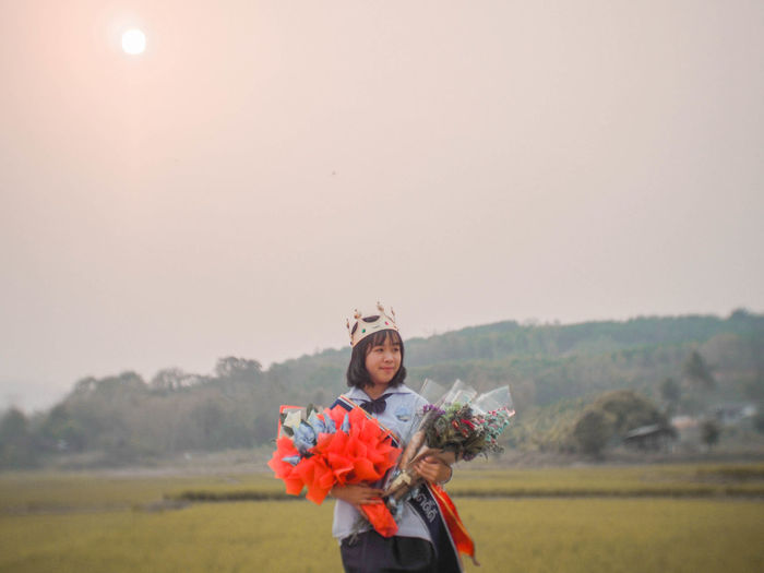 Young woman holding bouquets while standing on field against sky during sunset